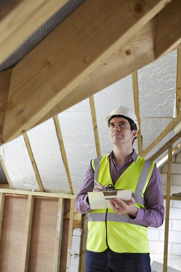 Inspetor de construção que olha o telhado da propriedade nova fotografia de stock royalty free