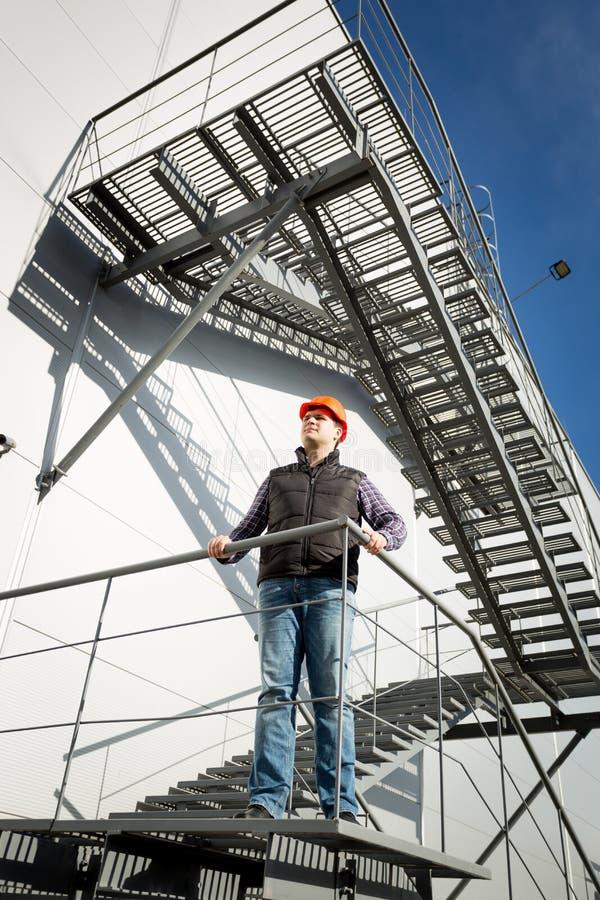 Inspetor do controle da construção que está na escadaria do metal foto de stock royalty free