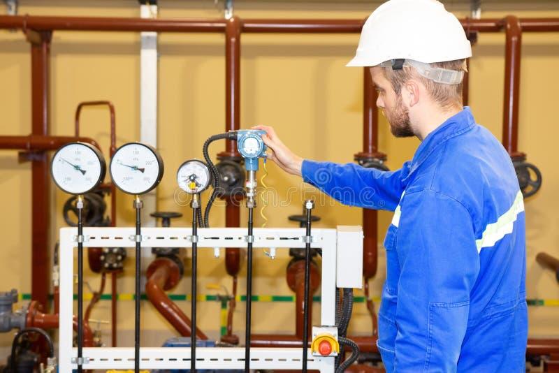 Inspetor do técnico na planta de refinaria que verifica a pressão fotografia de stock royalty free