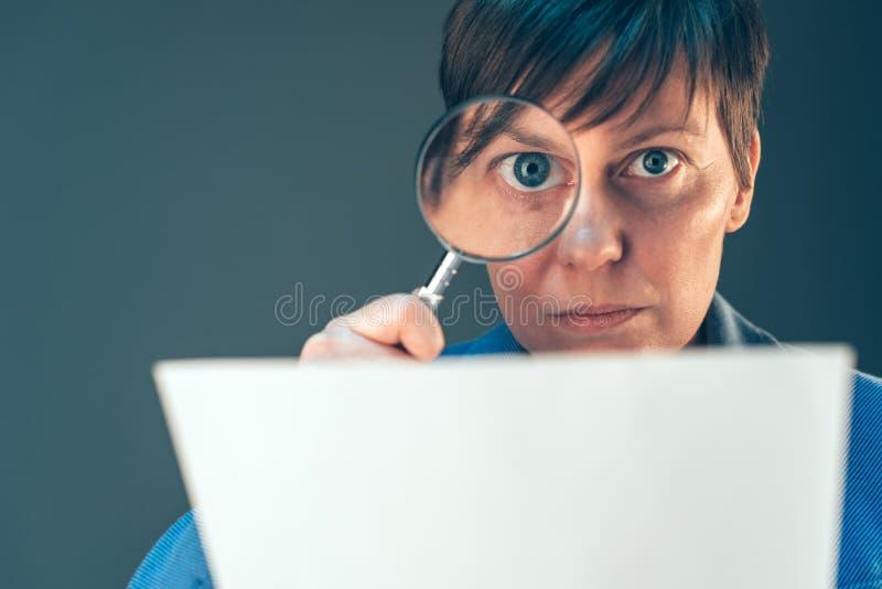 Inspetor fêmea do imposto que olha o original com lupa foto de stock