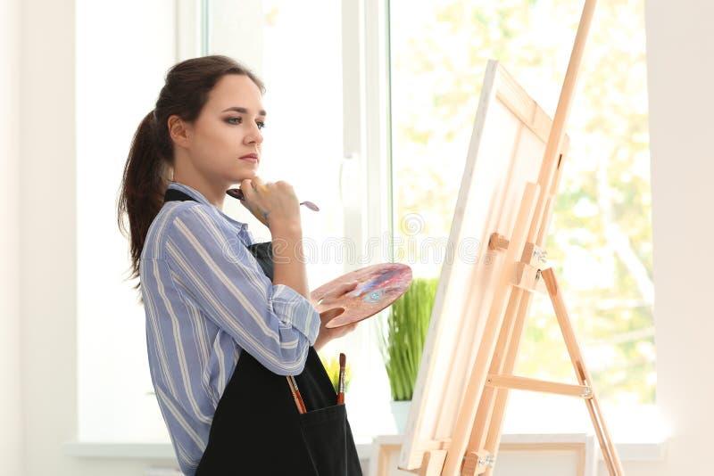Inspiração de espera do artista fêmea na oficina foto de stock royalty free