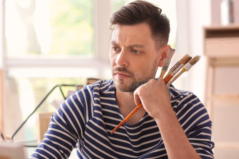 Inspiração de espera do artista masculino na oficina fotos de stock royalty free