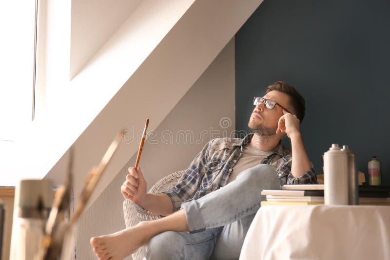 Inspiração de espera do artista masculino na oficina imagem de stock