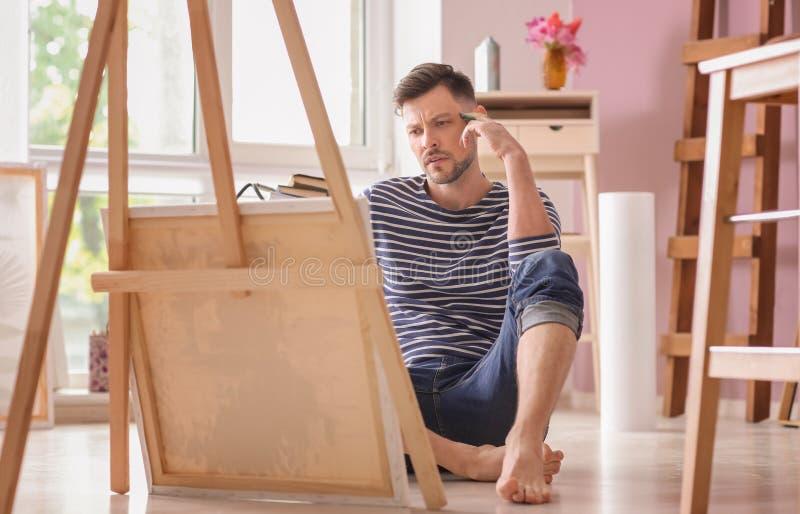 Inspiração de espera do artista masculino na oficina imagens de stock