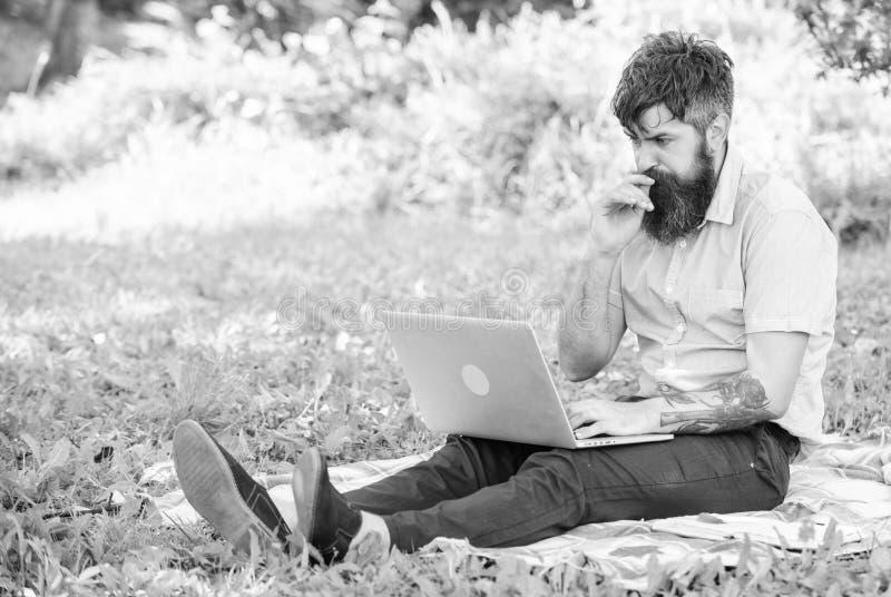 Inspiração para publicar em blogs Blogger que torna-se inspirado por natureza Homem farpado com fundo da natureza do portátil O B fotos de stock