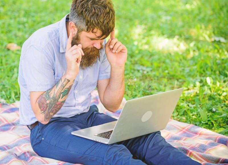Inspiração para publicar em blogs Procurando a inspiração O homem farpado com portátil senta o fundo da natureza do prado Blogger fotos de stock royalty free