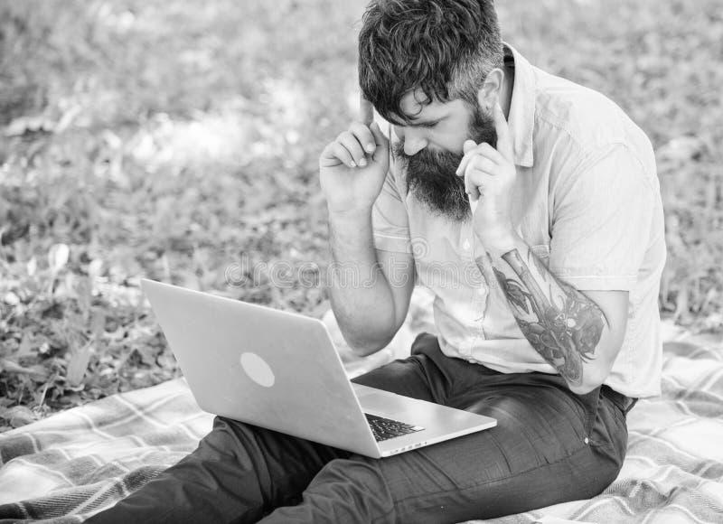 Inspira??o para publicar em blogs Procurando a inspira??o O homem farpado com port?til senta o fundo da natureza do prado Blogger imagens de stock
