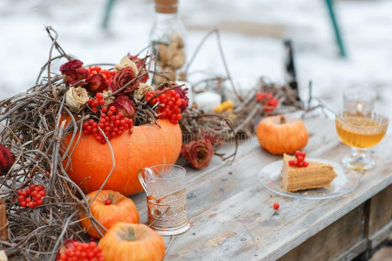 Inspiración de Halloween Todavía del otoño vida calabaza, rosas secas, torta de miel del viburnum en un florero ramitas En la tab foto de archivo
