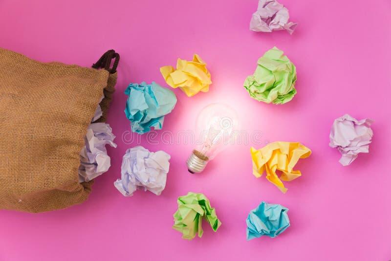 Inspiratieconcept met verfrommelde kleurendocument en gloeilamp stock afbeeldingen