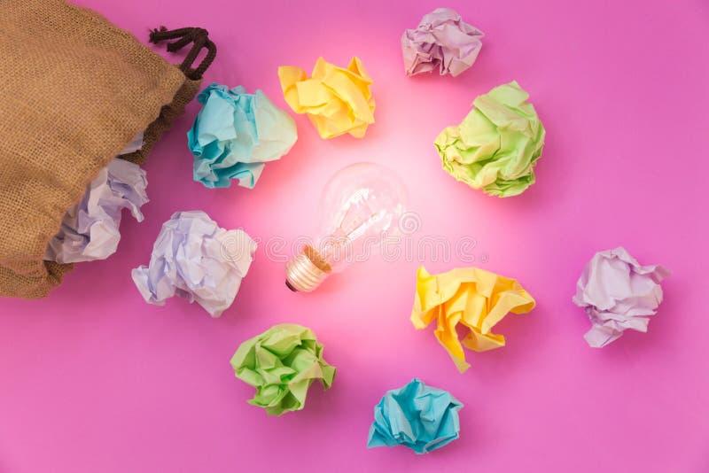 Inspiratieconcept met verfrommelde kleurendocument en gloeilamp stock foto