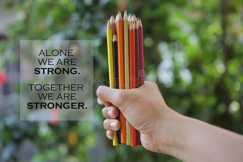 Inspiratinal quote - Alone we are strong. Together we are stronger. With young woman hand holds bunch of pencil colored and blurry stock images