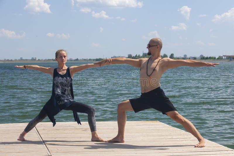 Inspiration de yoga Vue supérieure - les couples du beaux homme et femme minces en bonne santé gais font le virabhadrasana photo stock