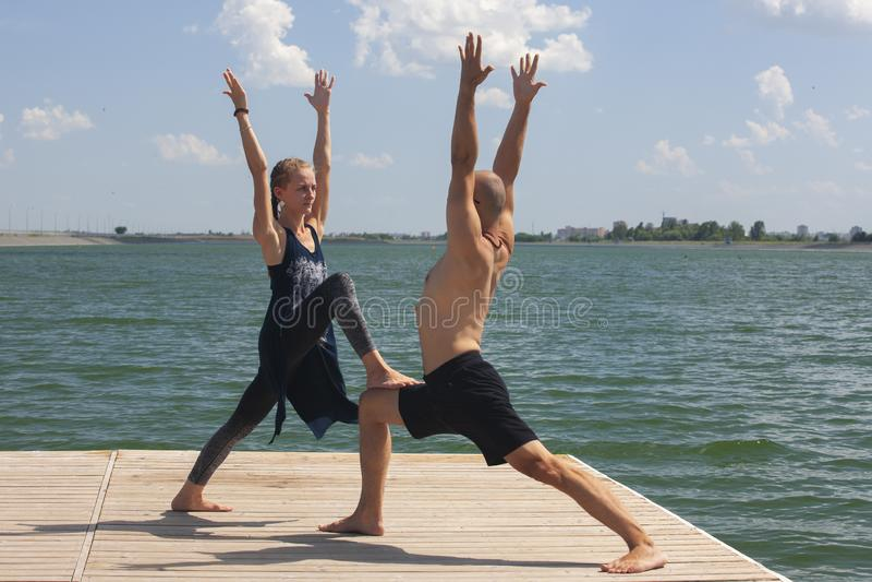 Inspiration de yoga Vue supérieure - les couples du beaux homme et femme minces en bonne santé gais font le virabhadrasana photographie stock libre de droits