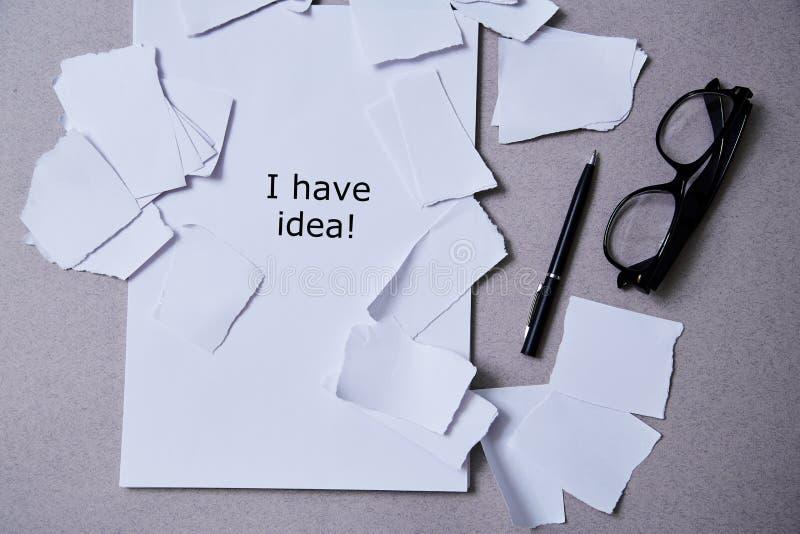 Inspiration, inblick eller bra idébegrepp: sönderrivet papper runt om ett tomt ark av papper arkivfoton