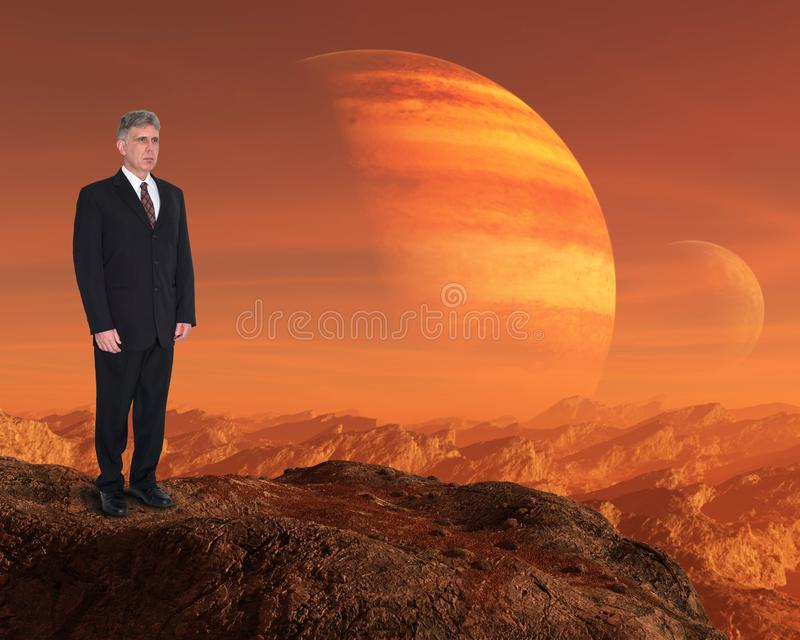 Inspiration, Success, Goals, Business, Sales, Marketing. A businessman stands on a rock or cliff above a surreal alien world landscape with red planets. Abstract royalty free stock image
