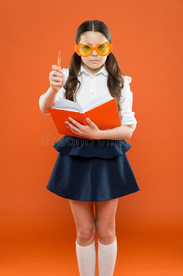 Inspiration for writing. get information from book. happy school girl in uniform and party glasses. small child with. Notebook. literature lesson education stock images