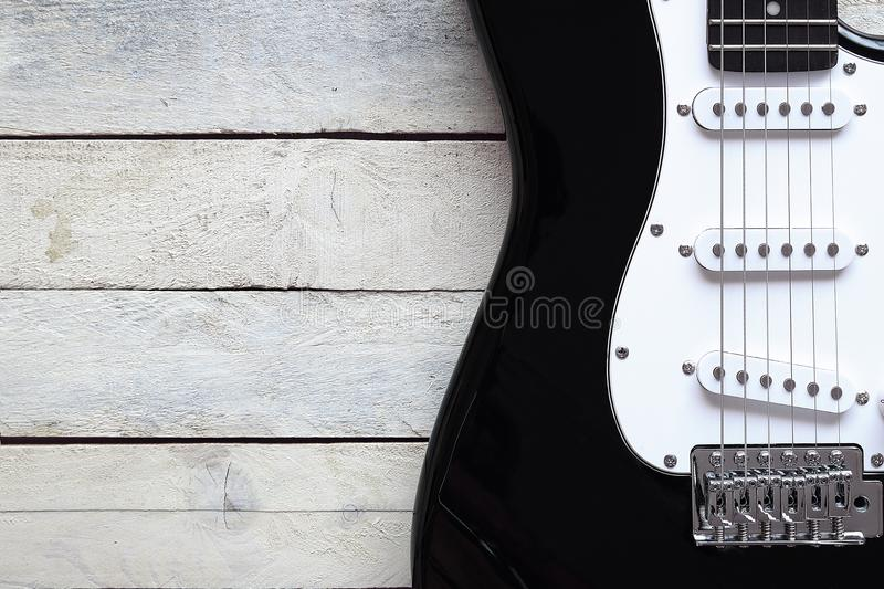Inspirational background with a guitar on a wooden table while composing. Top view and a copy space for editor`s text stock image