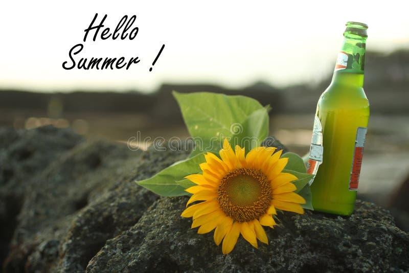 Inspirational de Zomergroeten van citaathello Met zonnebloembloesem op overzeese rots leggen en een fles die het verse bier nieuw stock foto