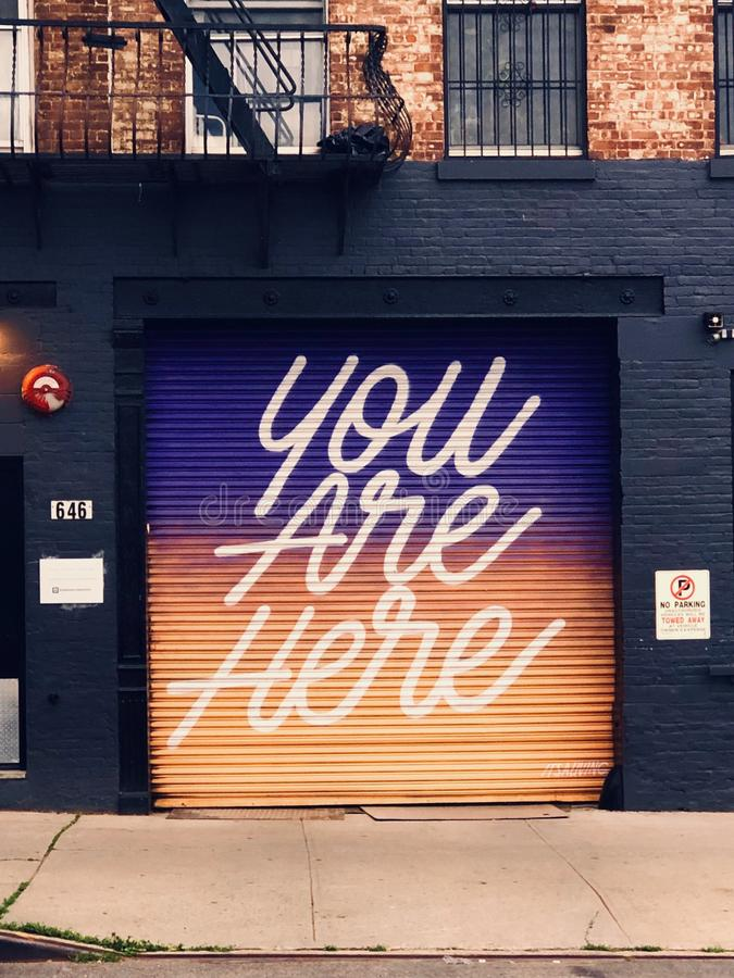 Inspirational garage door mural in Brooklyn, NY with gradient background. stock image