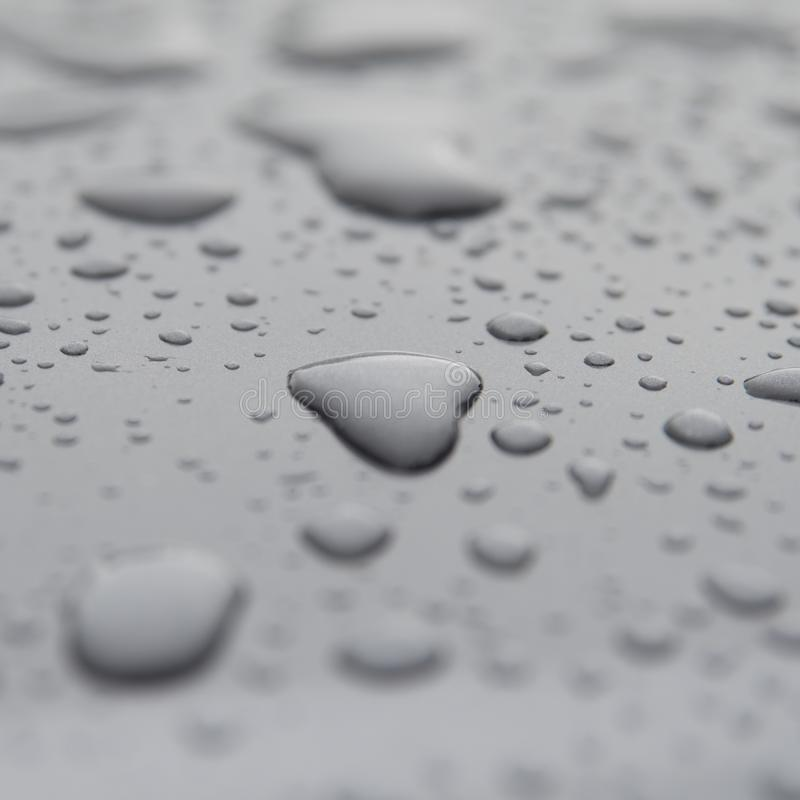 Inspirational heart shaped rain water drop on gray surface. Water droplets of rain on wet surface . love the rain when it falls. clean water supply comes from stock images