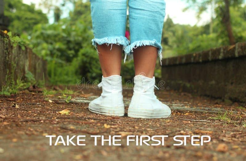 Inspirational motievencitaat treft de eerste maatregel Met voeten van jonge vrouw in witte tennisschoenen die zich van rug bevind royalty-vrije stock fotografie