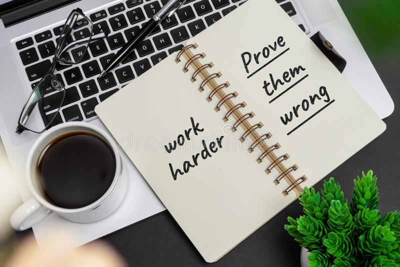 Inspirational and motivation life and business quote on notepad. With laptop - Work Hard. Prove Them Wrong stock photos