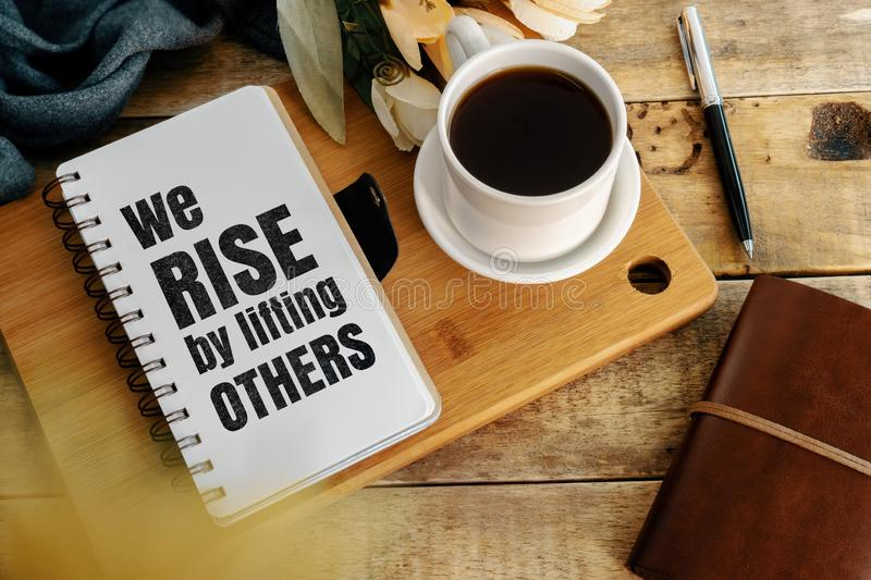 Inspirational and motivation life quote on notepad. Inspirational and motivation life quote on notepad - We Rise by Lifting Others royalty free stock photo