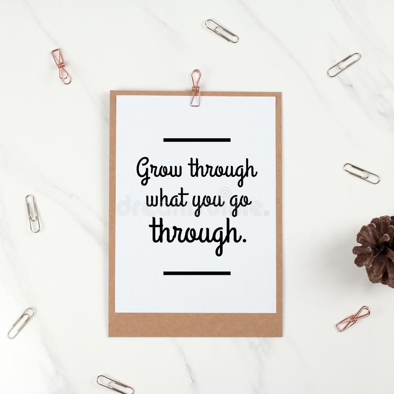 Inspirational motivational quote `Grow through what you go through`. On sheet of note paper and paper clips background stock image