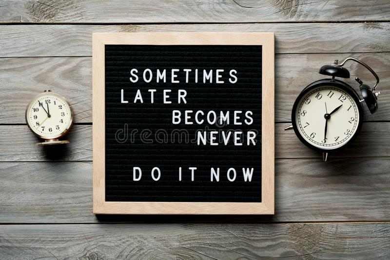 Inspirational motivational quote Sometimes later becomes never. Do it now words on a letter board on wooden background near. Vintage alarm clocks. Success and stock image