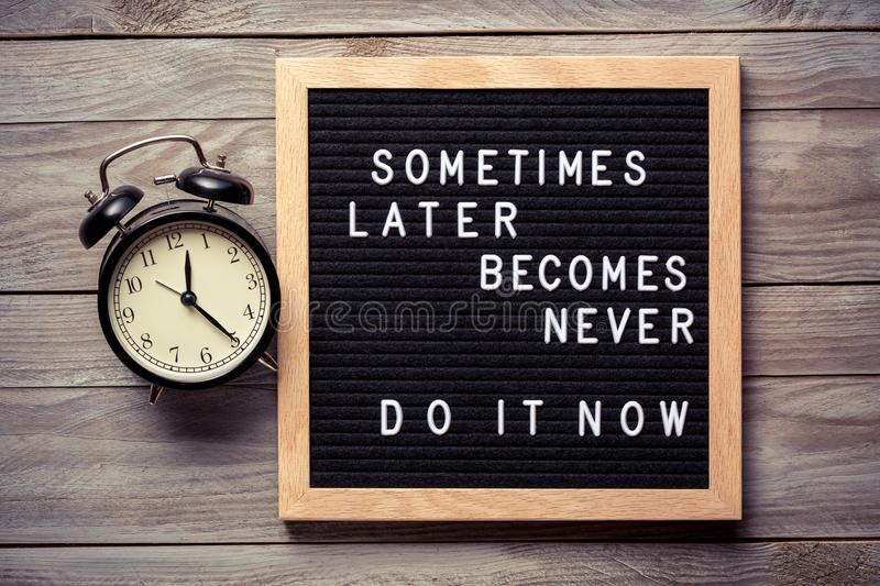 Inspirational motivational quote Sometimes later becomes never. Do it now words on a letter board on wooden background near stock images