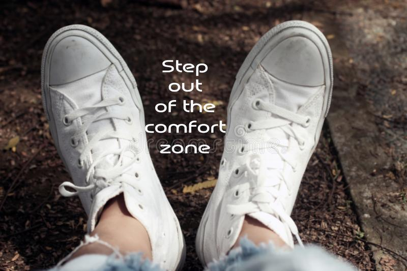 Inspirational motivational quote- Step out of the comfort zone. With relax feet of young woman in white sneakers background stock image