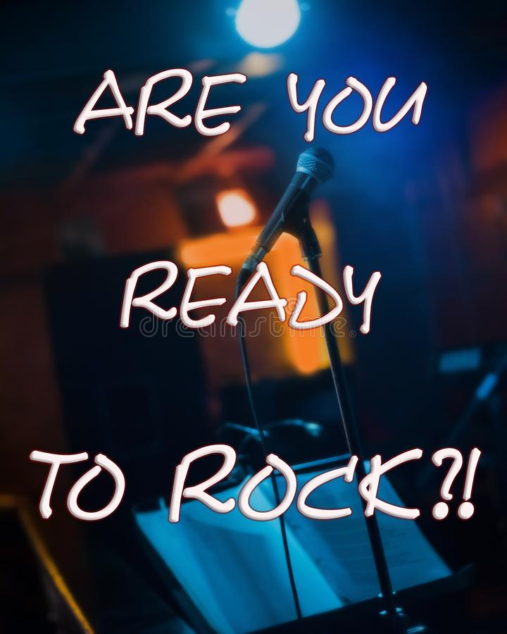 Inspirational motivational quote `Are you ready to rock?!`. With microphone on a stage fixed on a stand and ready before beginning of a concert in a pub, low royalty free stock images
