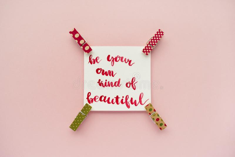 Inspirational quote be your own kind of beautiful handwritten with watercolor in calligraphy style, miniature clothespins on a pal stock photography