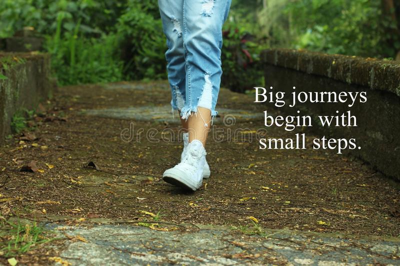 Inspirational quote- Big journeys begin with small steps. With feet of young woman walking surrounding with fresh green nature royalty free stock photo