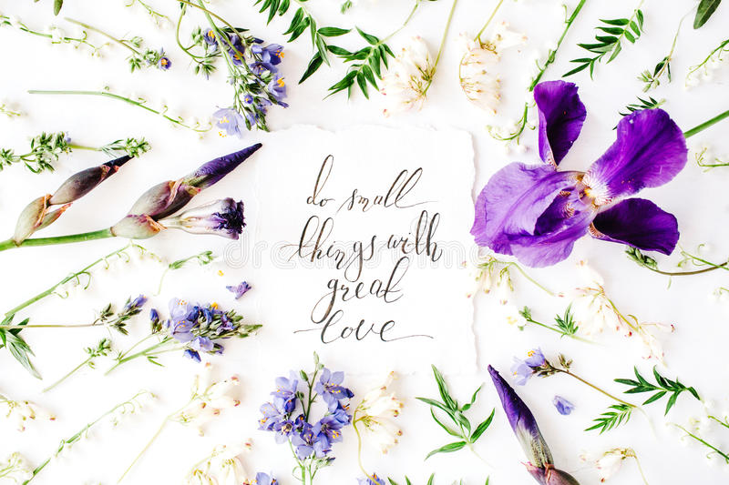 Inspirational quote `do small things with great love` written in calligraphy style on paper with wreath frame with purple iris flo. Wer and lilies isolated on stock photos