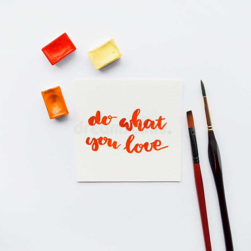Inspirational quote do what you love , watercolor cuvettes, paint brushes on a white background. Artist workspace. royalty free stock photos