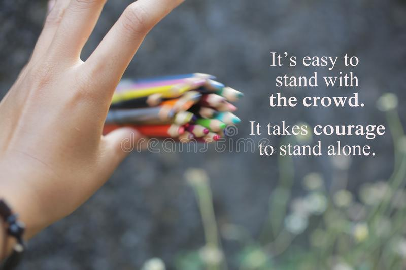 Inspirational quote - It is easy to stand with the crowd. I takes courage to stand alone. stock photography