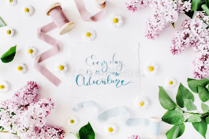 Inspirational quote `everyday is a new adventure` written in calligraphy style on paper with wreath frame with lilac and chamomile royalty free stock photos