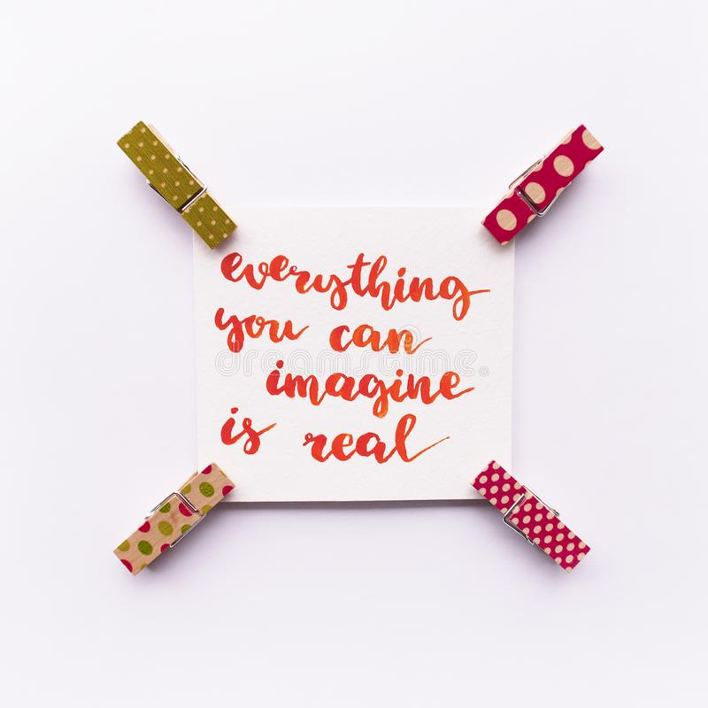 Inspirational quote Everything you can imagine is real handwritten with watercolor in calligraphy style, miniature clothespins on stock image