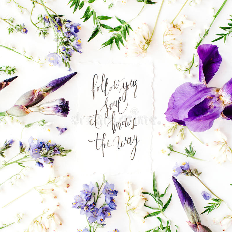 Inspirational quote `follow your soul it knows the way` written in calligraphy style on paper with wreath frame with purple iris. Flower and lilies isolated on stock photography