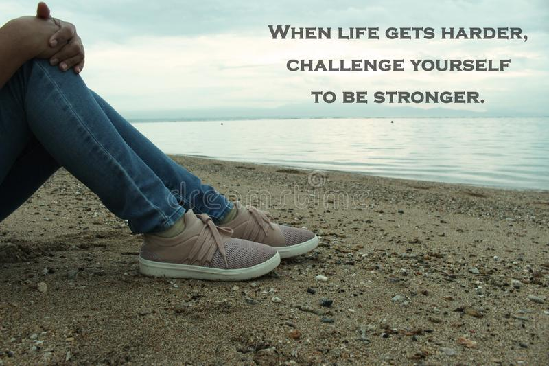 Inspirational Quote-When life gets harder, challenge yourself to be stronger. With a thoughtful young woman sitting in the beach stock images