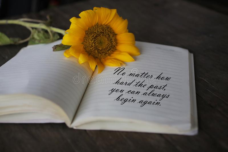 Inspirational quote - No matter how hard the past you can always begin again. With notes on a book and sun flower blossom on. Note to self and self reminder stock photo