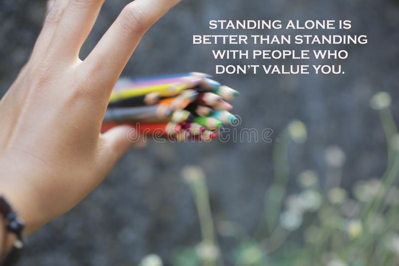 Inspirational quote - Standing alone is bettern than standing with people who do not value you. With motion bunch of pencils color royalty free stock image
