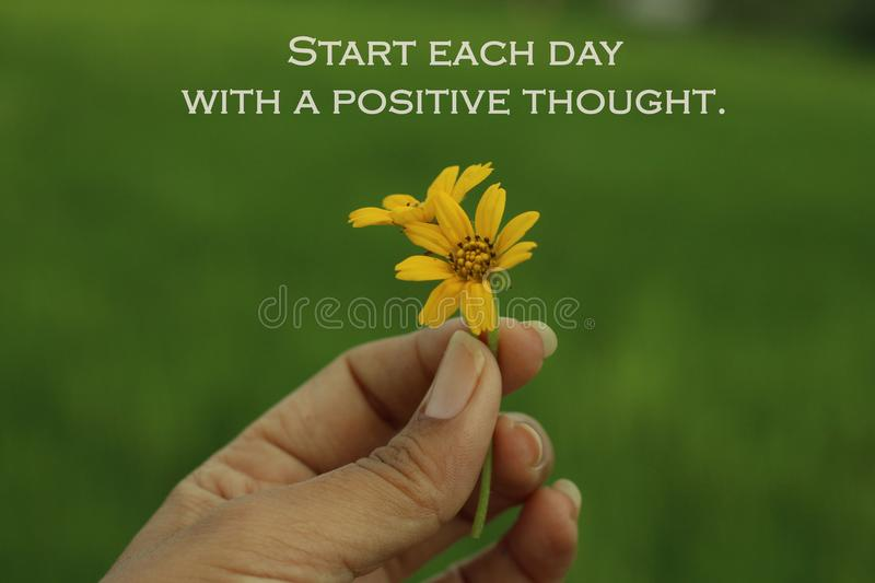 Inspirational words - Start each day with a positive thought. With two cute bautiful little daisy flowers in hand. stock images