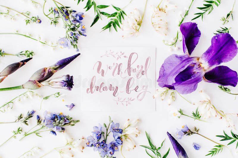 Inspirational quote `work hard dream big` written in calligraphy style on paper with wreath frame with purple iris flower and royalty free stock photos