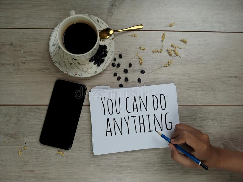 Inspirational quote - You can do anything. With a cup of hot black morning coffee, roasted coffee beans, hand phone, and a young stock photo