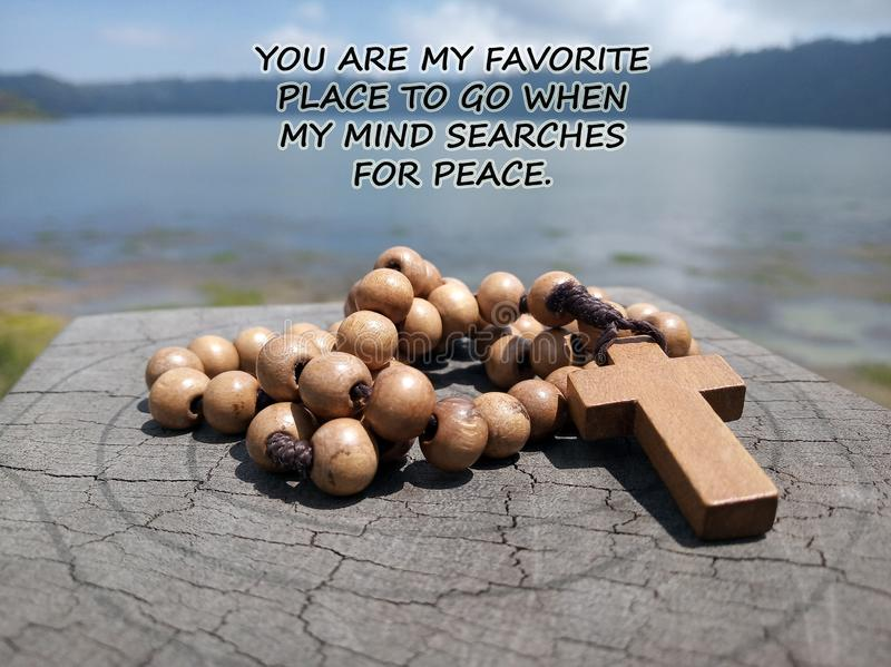 Inspirational quote - You are my favorite place to go when my mind searches for peace. With blue lake background & wooden rosary. On wood  with Jesus Christ stock images