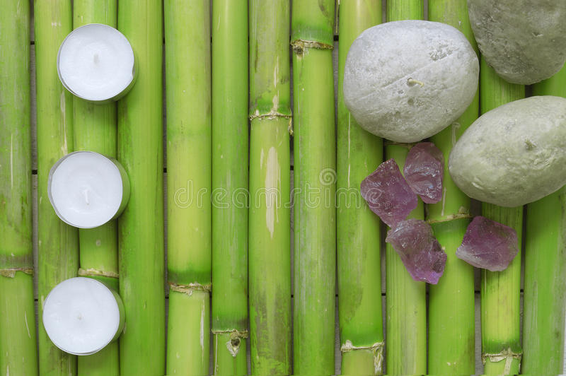 Inspirational scene with three candles aligned, stones and gemstones on a natural green bamboo background. royalty free stock images