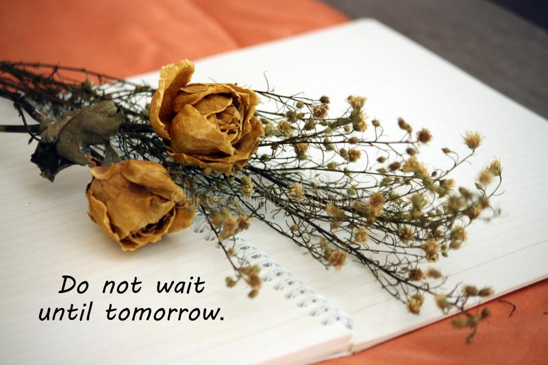 Inspirational words - Do not wait until tomorrow. Notes on a notebook concept with dried roses flowers. royalty free stock photos