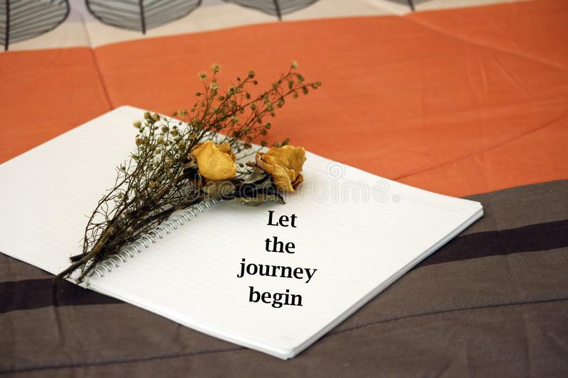 Inspirational words - Let the journey begin. Notes on notebook concept with dried roses. royalty free stock image